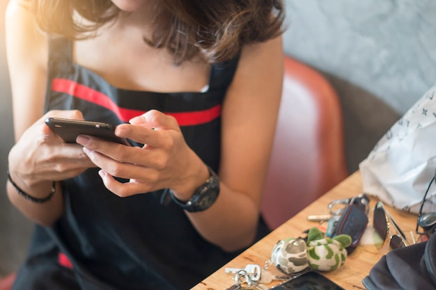 Hand of woman using smartphone on wooden table