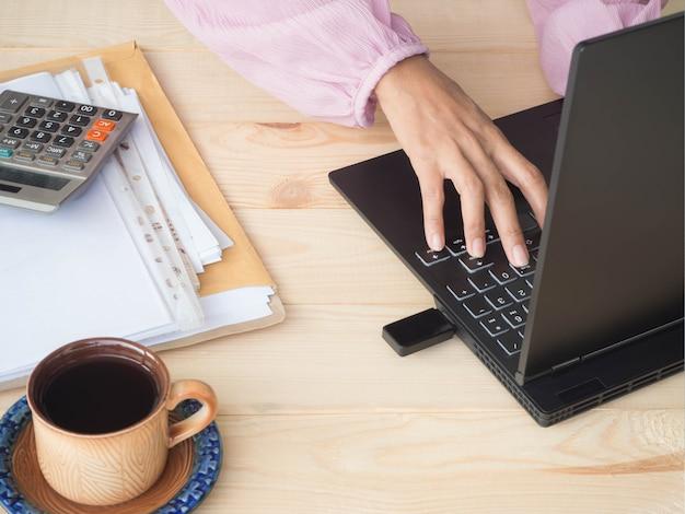 Рука женщина с документом, ноутбуком, калькулятором на деревянных фоне.