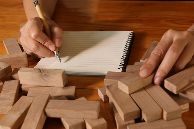 Hand of woman writing on note book and holding wooden block