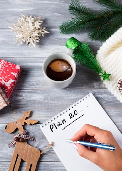 Hand of woman writing on notepad christmas greetings withcup of tea, decoration on wooden