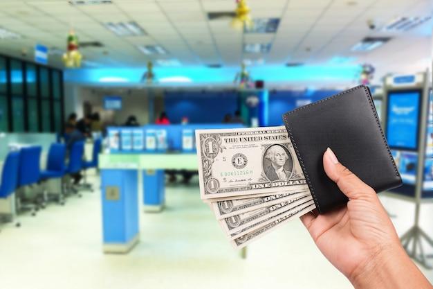 手の女性は、銀行の背景に黒の財布にお金を入れる