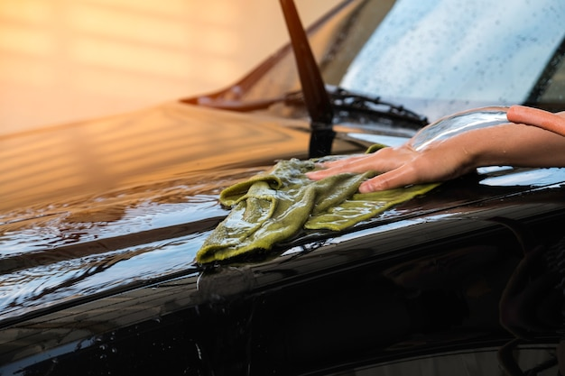 Hand women hold water over the black car for washing with microfiber cloth