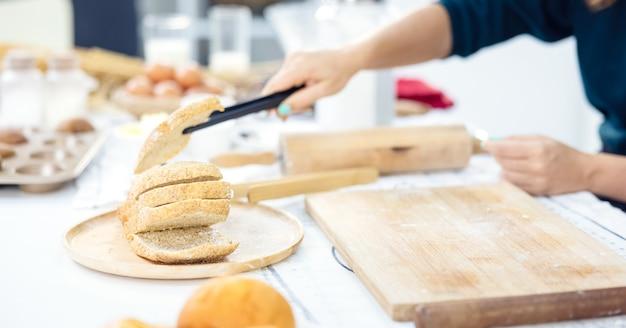 Руки женщины берут золотой кукурузный хлеб на кухне