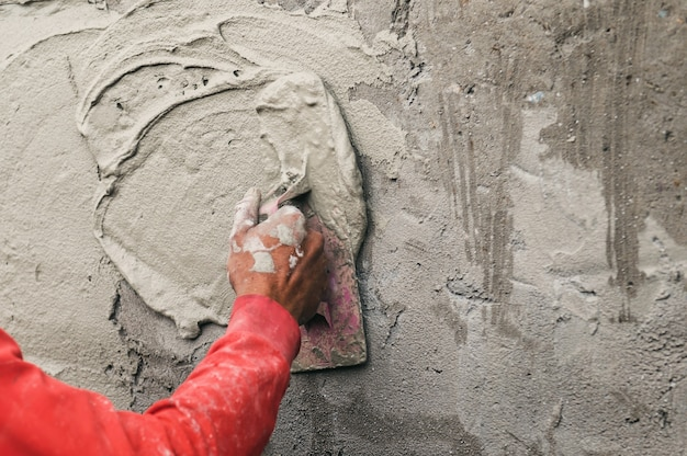 Hand of worker plastering cement at wall for building house in construction site