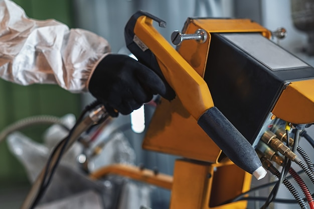 The hand of a worker in protective clothing holding a powder coating sprayer