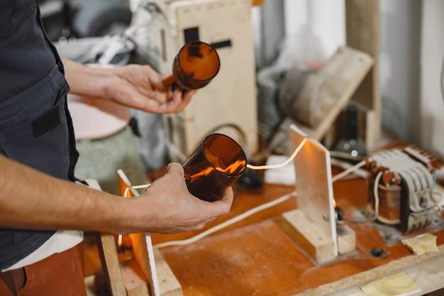 空のボトルを持つハンドワーカー。男の手のクローズアップ。生産の概念。