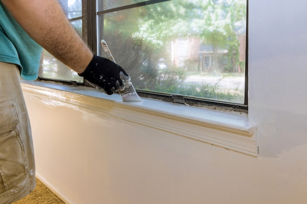 Hand of worker with gloves in the painting window molding trim