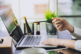 Hand working marketing plans with laptop computer in office