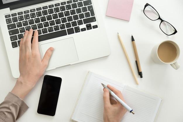 노트북에서 일하는 손, 펜을 들고 다른