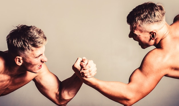 Ручная борьба, соревнования. руки или руки человека. мускулистая рука. двое мужчин по армрестлингу. соперничество, крупный план мужского армрестлинга. мужчины меряют силы, оружие.