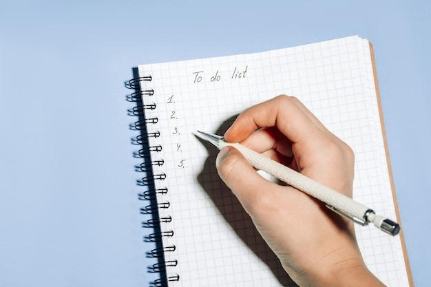 파란색 배경에 있는 노트북에 할 일 목록을 손으로 씁니다. 작업 장소 및 계획 개념, 상위 뷰.