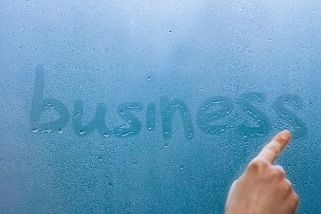 손 방울 배경으로 창 유리에 사업을 씁니다.