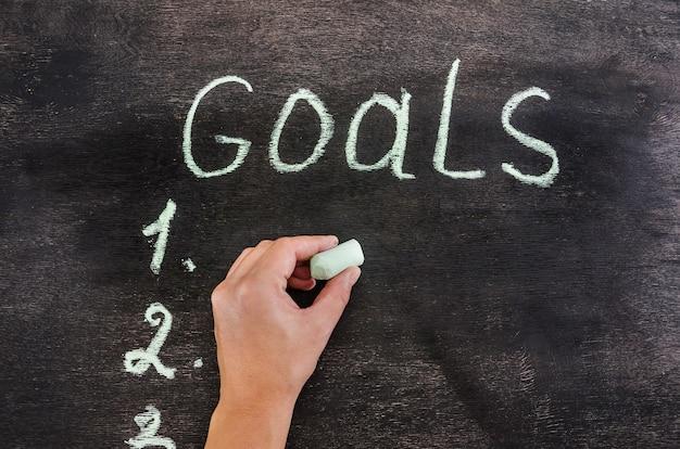 Hand writes in chalk on a blackboard the word goals