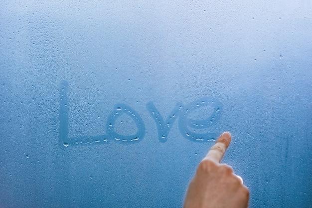 손 방울 배경으로 창 유리에 사랑을 씁니다.