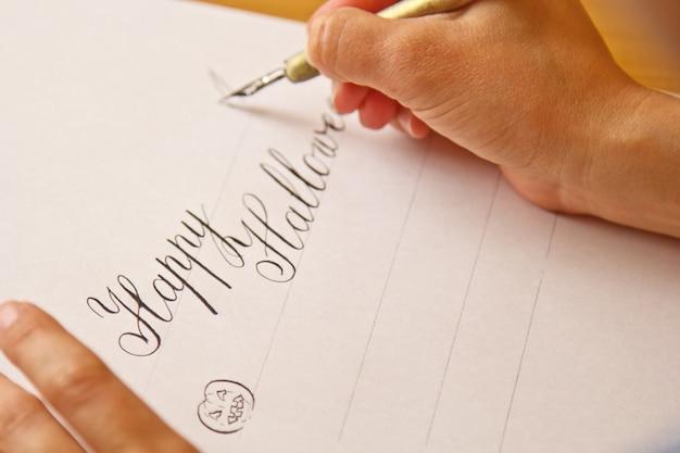 손으로 더러워진 펜으로 흰 종이에 해피 할로윈 줄무늬가 씁니다.