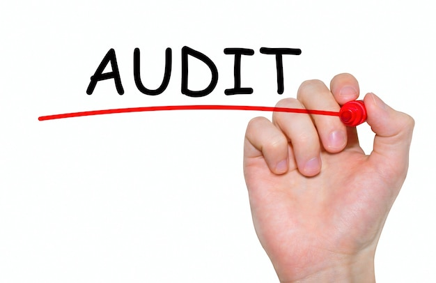 Hand writing audit, with red marker on transparent wipe board.