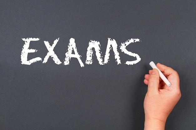 Hand writing chalk on a blackboard text: exams.