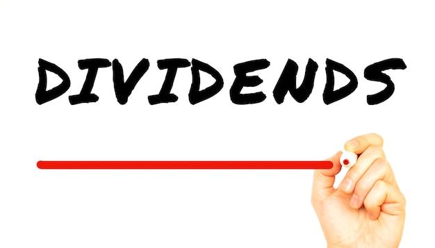 赤いマーカーでdividendsを手書き。白い背景で隔離。ビジネスコンセプト。