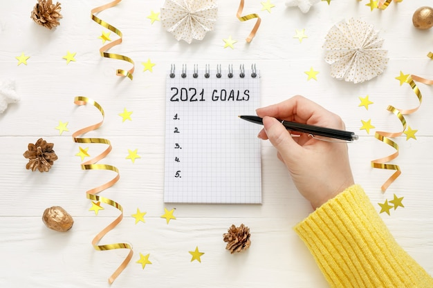Hand writing goals for new year in new notebook on white wooden desk