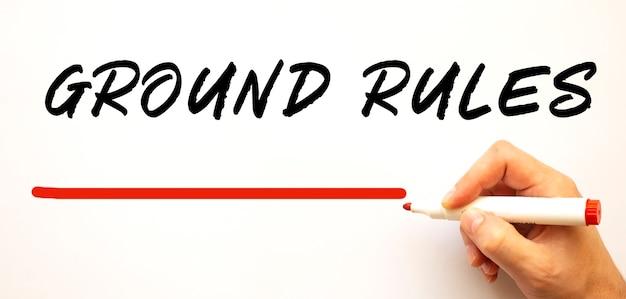 빨간색 표시와 함께 지상 규칙을 작성하는 손. 흰색 배경에 고립. 비즈니스 개념.