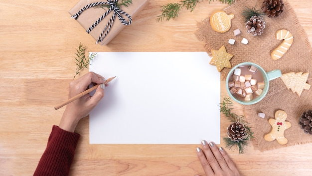 Hand writing mockup postcard for to do list and hot chocolate with marshmallow, cookie on wooden background. winter christmas and happy new year concept.