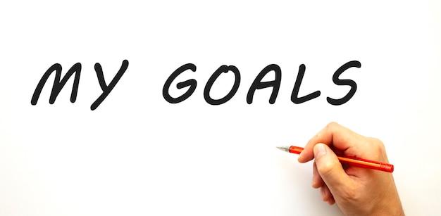 펜으로 내 목표를 작성하는 손. 흰색 배경에 고립. 비즈니스 개념.