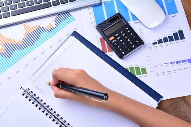 木製のテーブルにグラフ、チャート、キーボード、マウス、電卓で空白のノートに手書き