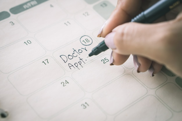 Hand writing remind note doctor appointment on calendar