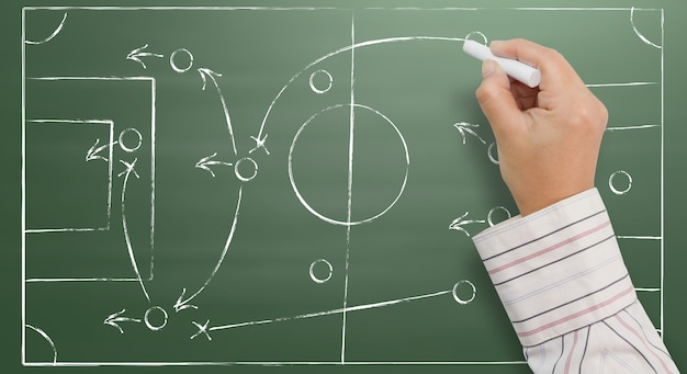 Hand writing a soccer game strategy on a blackboard