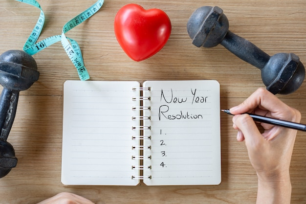 Hand writing text new year resolutions on notebook for sport concept