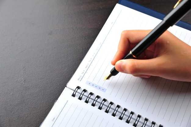 Hand writing using fountain pen on a notebook