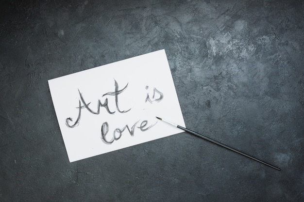 Hand written 'art is love' text on white paper with paint brush over slate surface