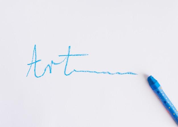 Hand written art text near blue crayon on a white background