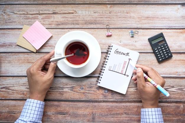 사무실 책상에서 메모장에 성장 차트를 작성하는 손 프리미엄 사진