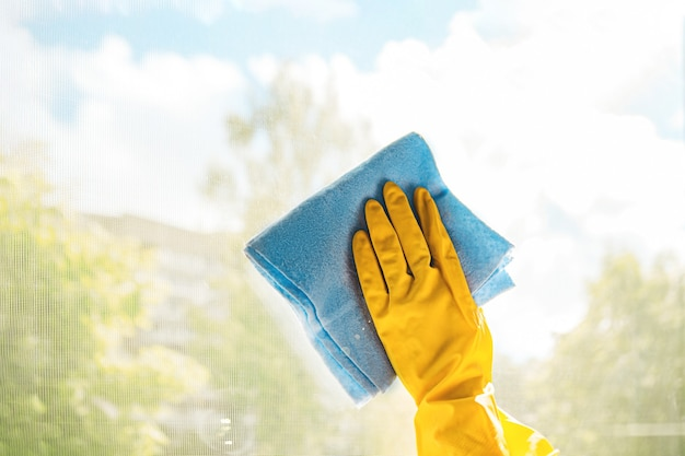 Hand in a yellow glove cleans the window with a blue rag