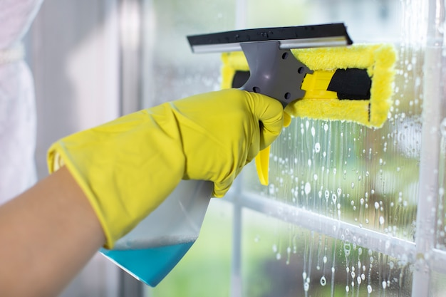 Hand in yellow glove wipes window with cleaning scraper. house cleaning
