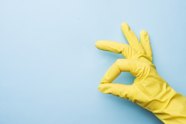 Hand in yellow gloves for cleaning on blue background.