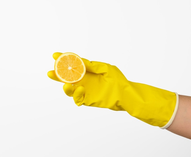 Hand in a yellow latex cleaning glove holds half a lemon on a white background, close up