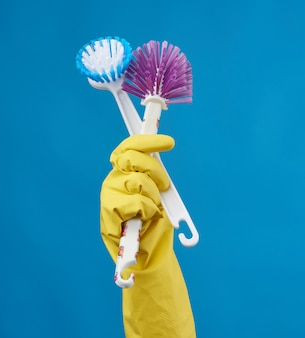 Hand in a yellow rubber glove for cleaning a house holds two plastic brushes