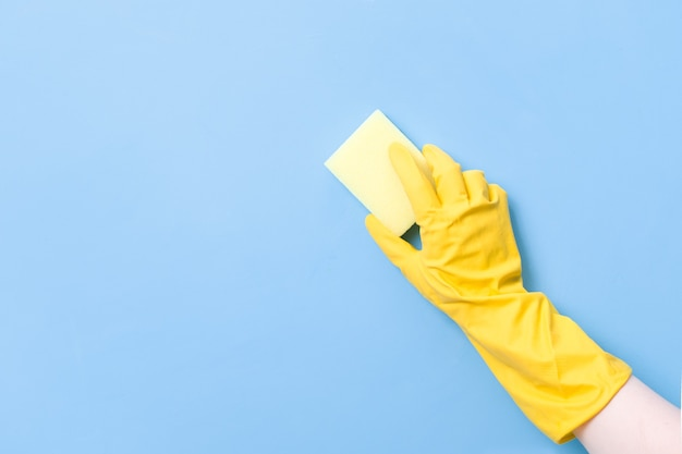 Hand in a yellow rubber glove holds a yellow sponge for washing dishes and cleaning