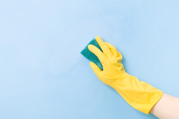 A hand in a yellow rubber glove holds a yellow sponge with a green rough side for cleaning complex dirt