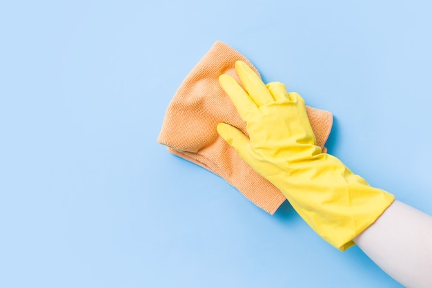 Hand in a yellow rubber glove washes the wall with an orange soft rag, cleaning and washing the walls