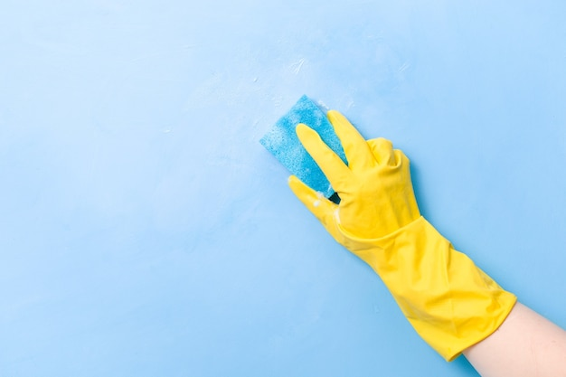 A hand in a yellow rubber glove washes a wall with a wet foamy blue sponge