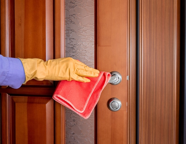 Hand in a yellow rubber glove wipes the door knob with a red rag. disinfect ingesited at home from bacteria and viruses. house cleaning