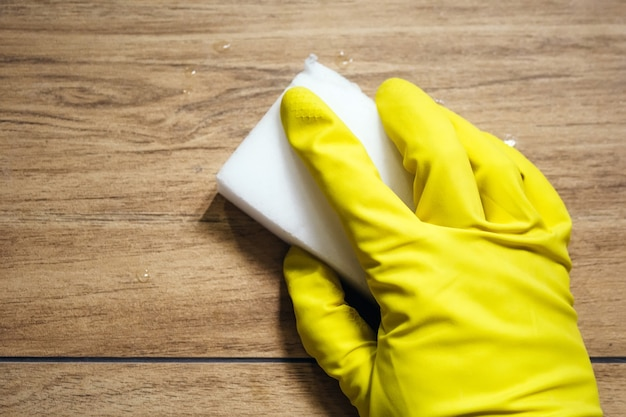 A hand in a yellow rubber glove wipes wet tile imitating a wooden surface with a white melamine sponge. cleaning in a modern bathroom. selective focus
