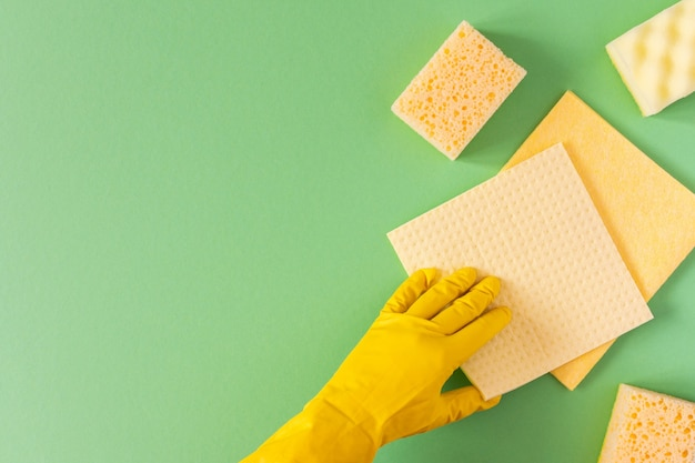 Hand in a yellow rubber glove with a cleaning sponges on a green background