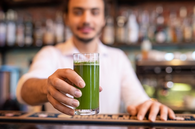 Hand of young barman holding glass of fresh vegetable smoothie over counter while giving it to one of guests of restaurant