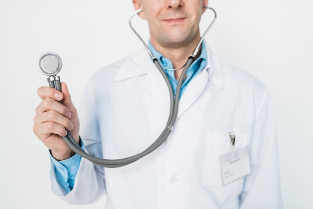 Hand of young contemporary doctor or clinician holding stethoscope in front of camera while posing in isolation