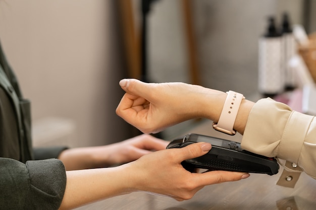 Hand of young contemporary female customer with smartwatch keeping her wrist over pos terminal during contactless payment