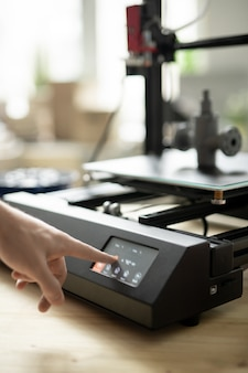 Hand of young designer pressing start button on control panel of 3d printer before beginning working process